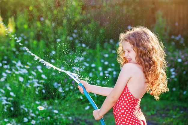 Bambina che gioca con un tubo da giardino.