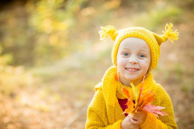 Bambina che gioca il giorno soleggiato di autunno