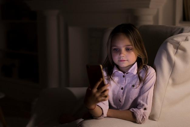 Bambina che gioca sul suo telefono a casa