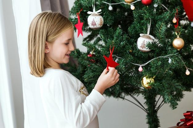 Bambina che gioca una stella rossa di albero di natale