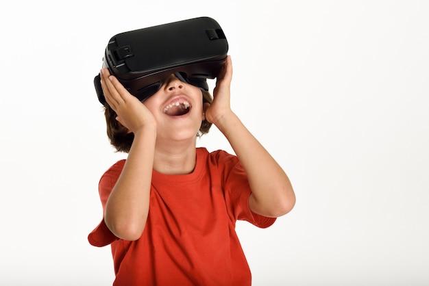 Bambina che guarda negli occhiali di vr e gesticola con le sue mani.