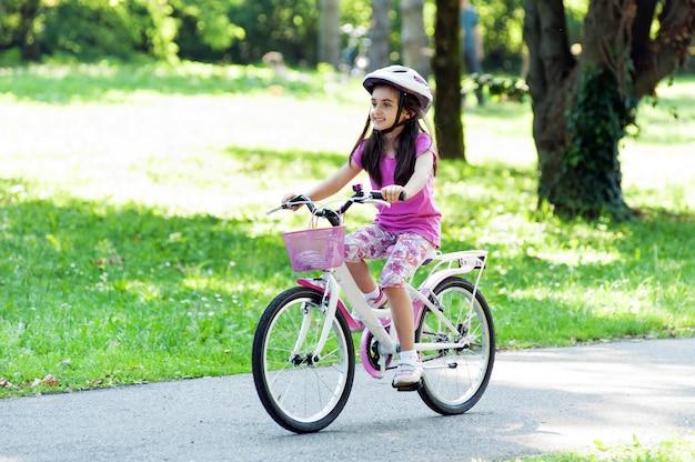 Bambina che guida la sua bicicletta in un parco