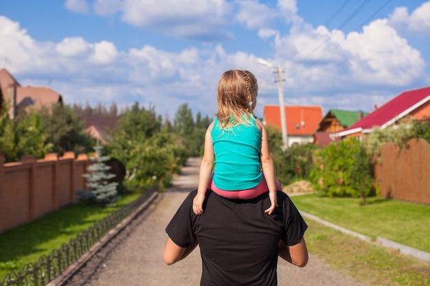 Bambina che guida sul giovane papà all'aperto