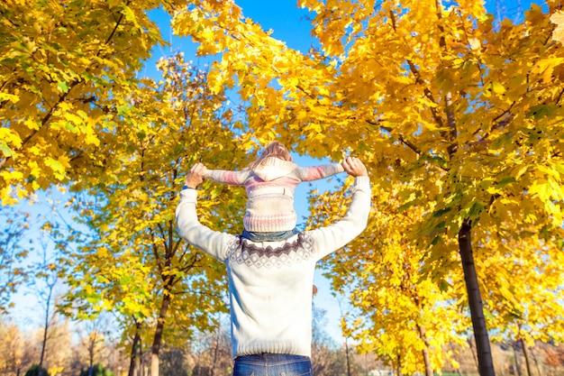 Bambina che guida sulle spalle del padre nel parco di autunno