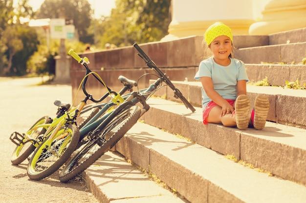 Bambina che guida una bici in una città