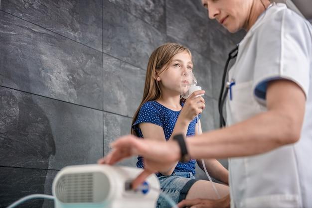 Bambina che ha un trattamento inalatorio medico con un nebulizzatore