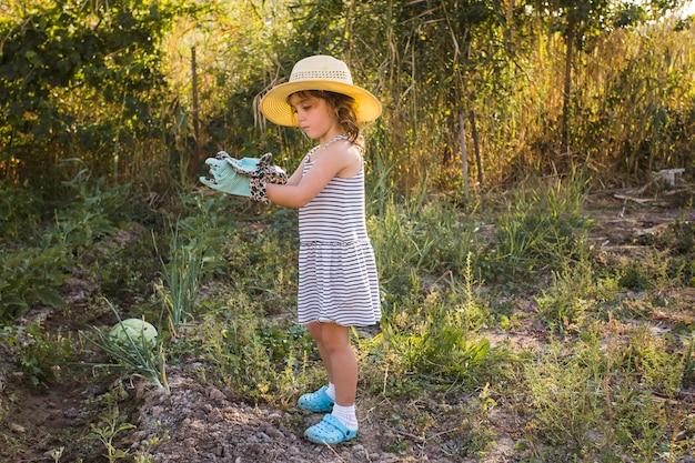 Bambina che indossa cappello in piedi nel campo