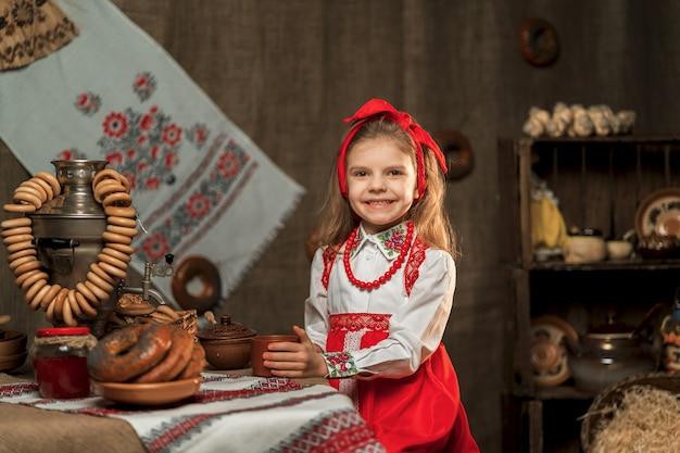 Bambina che indossa fascia rossa e camicia ornamentale che tiene tazza di tè dalla samovar che celebra maslenitsa