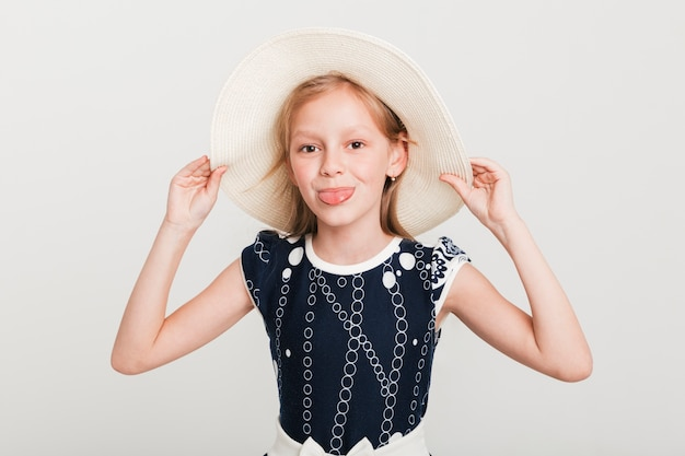 Bambina che indossa il cappello estivo