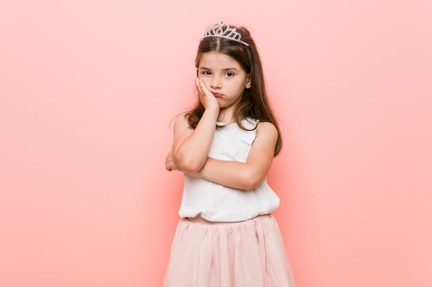 Bambina che indossa un look da principessa annoiata, affaticata e ha bisogno di una giornata di relax.