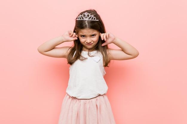 Bambina che indossa un look da principessa che copre le orecchie con le mani.