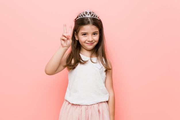 Bambina che indossa un look da principessa che mostra il numero due con le dita.