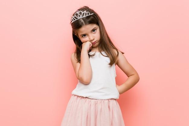 Bambina che indossa un look da principessa che si sente triste e pensieroso, guardando lo spazio della copia.