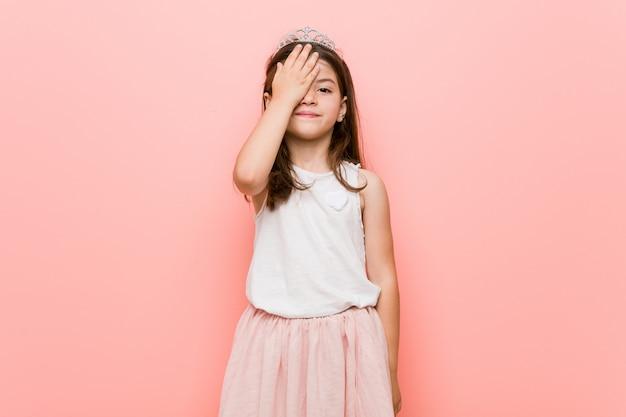 Bambina che indossa un look da principessa divertendosi coprendo metà del viso con il palmo