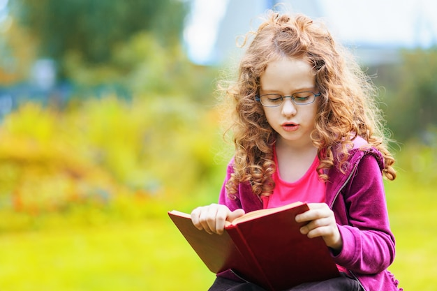 Bambina che legge il libro. concetto di educazione.