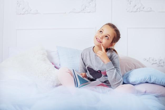 Bambina che legge un libro a letto. infanzia.