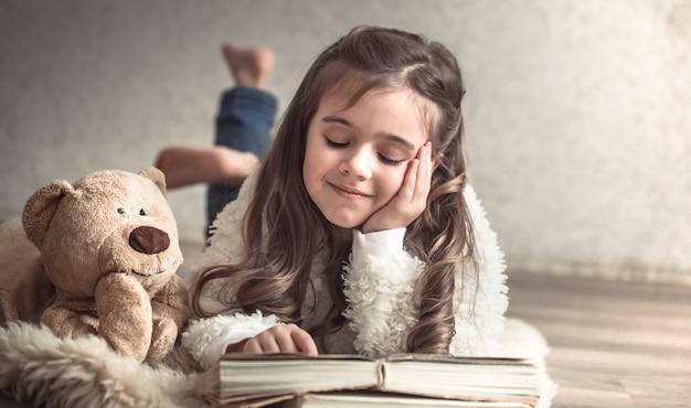 Bambina che legge un libro con un orsacchiotto sul pavimento, concetto di relax e amicizia