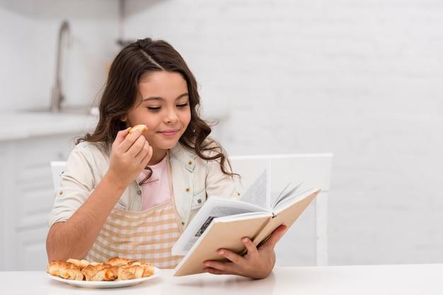 Bambina che legge un libro in cucina
