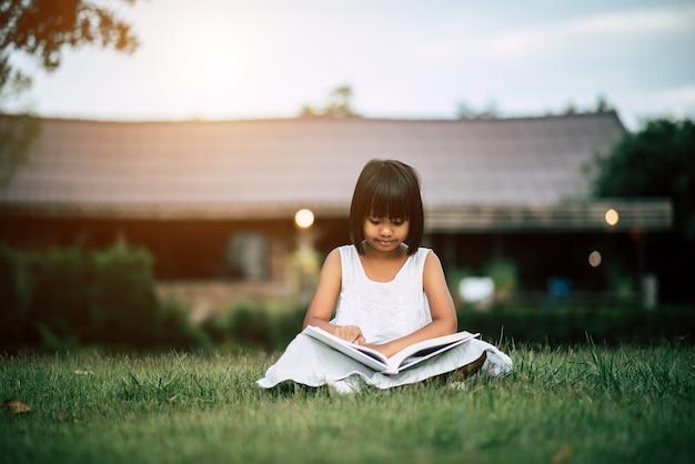 Bambina che legge un libro nel giardino di casa