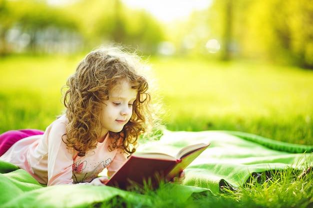 Bambina che legge un libro nel parco di primavera, tonificante foto.