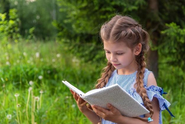 Bambina che legge un libro nella foresta