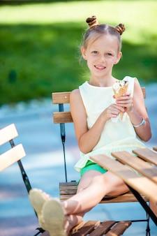 Bambina che mangia gelato all'aperto all'estate in caffè all'aperto