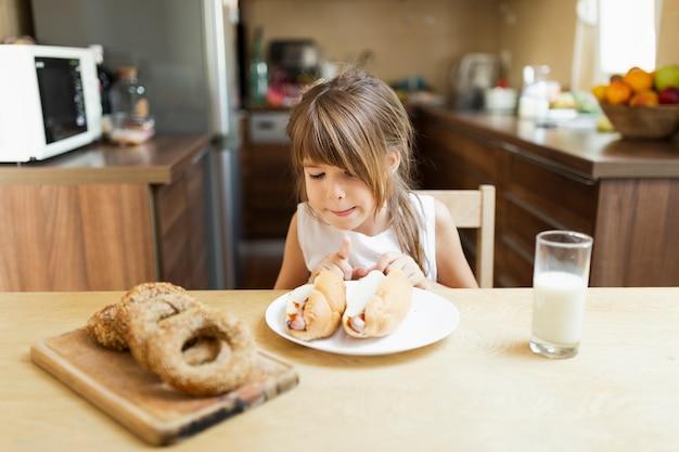 Bambina che mangia pasticceria e latte a casa