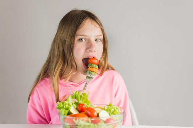 Bambina che mangia prima colazione sana contro fondo bianco