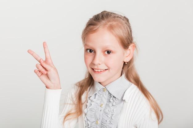 Bambina che mostra il segno di vittoria