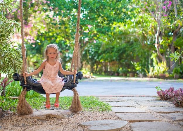 Bambina che oscilla su un'oscillazione nel cortile fiorito adorabile accogliente