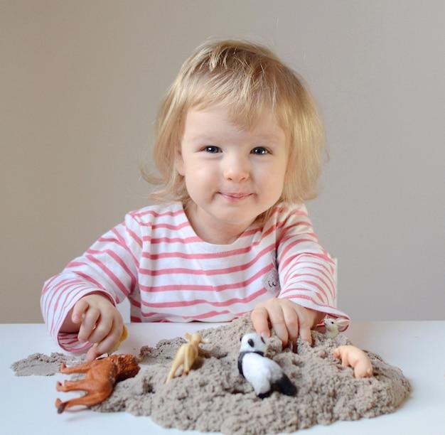 Bambina che paga con la sabbia cinetica e gli animali del giocattolo