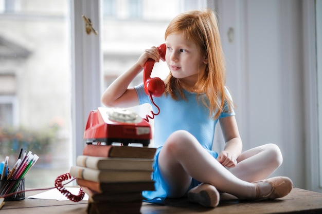 Bambina che parla su un telefono classico