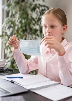 Bambina che partecipa alla lezione online all'interno