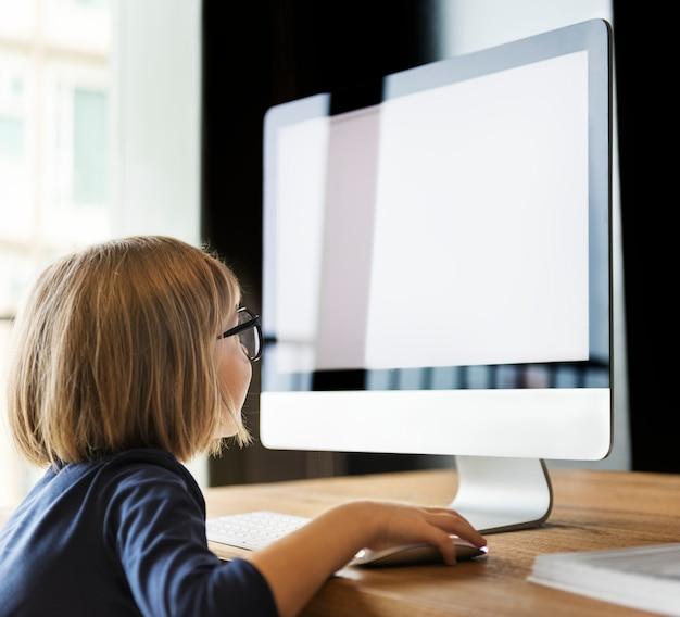 Bambina che per mezzo del concetto del computer