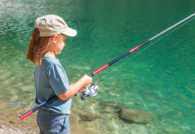 Bambina che pesca in montagna
