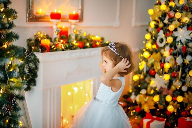 Bambina che posa in un vestito vicino allo specchio