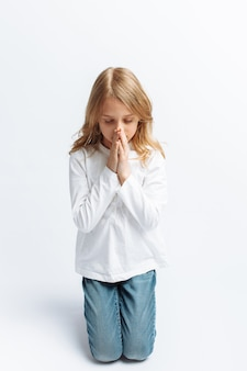 Bambina che prega in ginocchio a dio, comunione con dio, dolce e bella