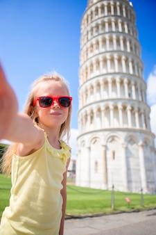 Bambina che prende selfie con la torre a pisa, italia