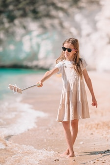 Bambina che prende selfie dal suo smartphone sulla spiaggia.