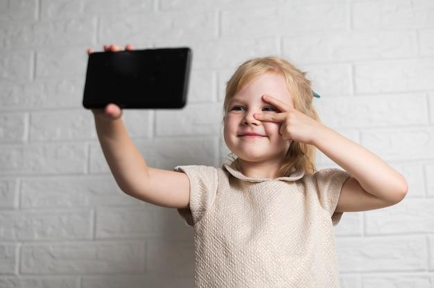 Bambina che prende un selfie
