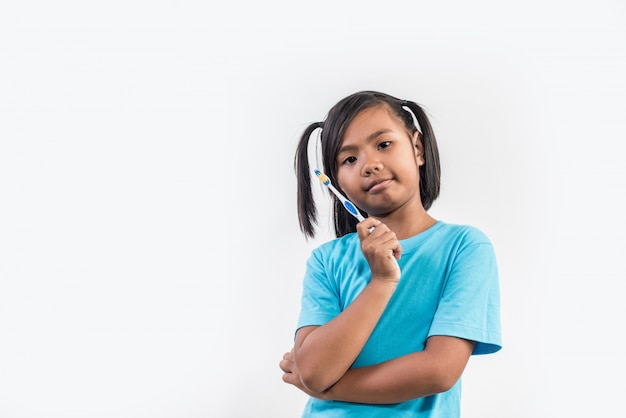 Bambina che pulisce i suoi denti nel colpo dello studio