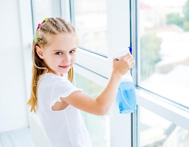 Bambina che pulisce la finestra