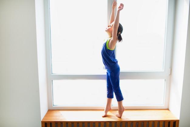 Bambina che raggiunge su allenamento a casa. ragazzo carino si sta allenando su un davanzale in legno al coperto. la piccola modella mora in abiti sportivi ha esercizi vicino alla finestra nella sua stanza.