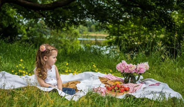 Bambina che riposa sul picnic con fragole
