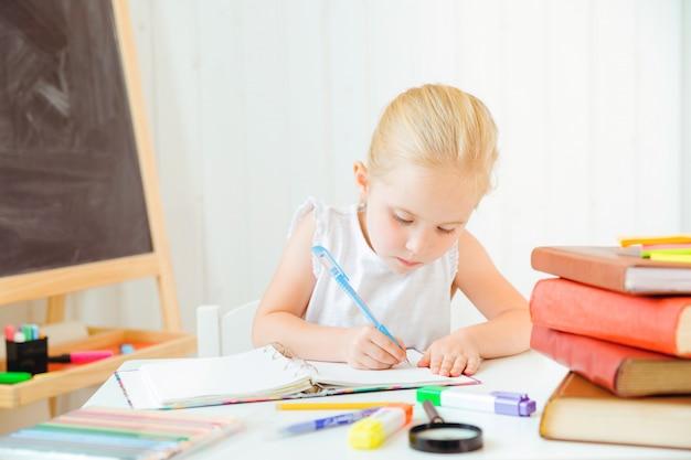 Bambina che sembra concentrata e concentrata nel fare i suoi compiti.