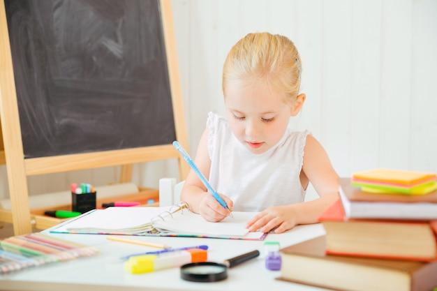 Bambina che sembra concentrata e concentrata sul fare i compiti.