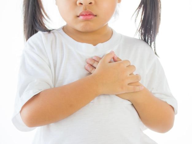 Bambina che sente il dolore al cuore e tenendo il petto, messa a fuoco a mano