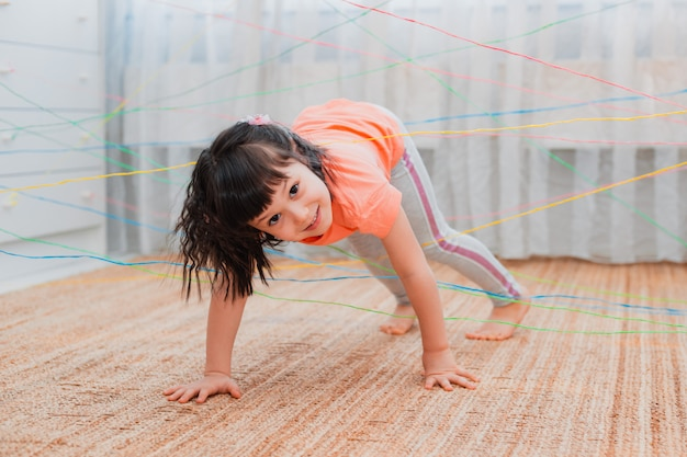 Bambina che si arrampica attraverso una tela di corda