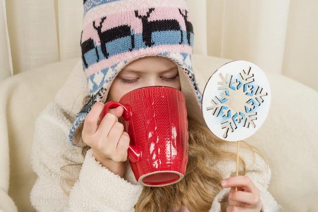 Bambina che si siede a casa con la tazza della bevanda calda.