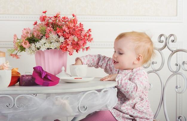 Bambina che si siede ad una tavola con tè e le decorazioni, ritratto, primo piano